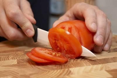 нож режет помидор